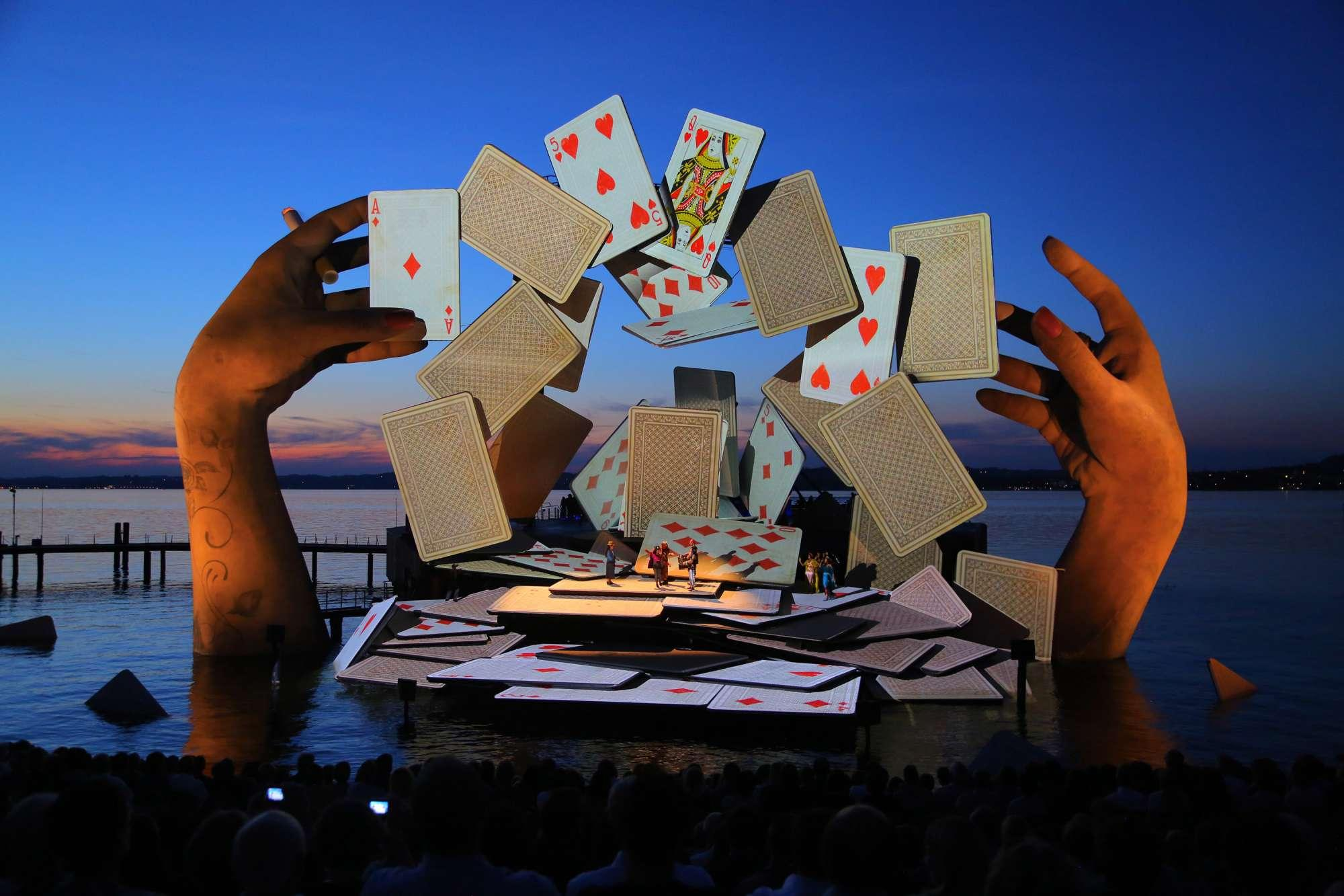 Scene from Es Devlin's Carmen set - playing card stage on river is flaked by large hands